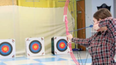 Senior Rachael Jaszczak pulls back her bow, getting ready to take her shot in the cafeteria on Feb. 11 during Archery Club practice. Photo by Creede McClellen.