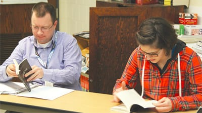 """Advanced Senior Social Science teacher Kyle Smith (left) sits beside senior Megan Tunell while skimming through """"Nigger: The Strange Career of a Troublesome Word"""" by Randall Kennedy on Feb. 20 in Room 235. Photo illustration by Creede McClellan"""