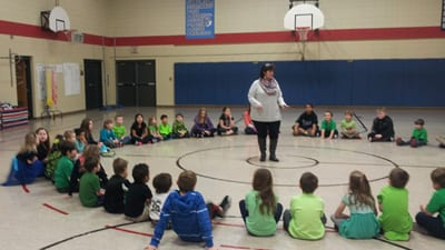 Teacher assistants works with 5th Grade helpers as all Kindergartners start the morning with structured movement activities, games, and breakfast.
