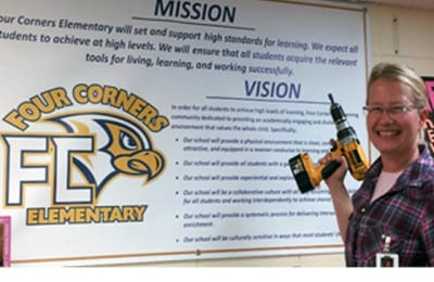 Ms Constance Putting up Mission and Vision Banner at Four Corners Elementary School | Explore Superior©